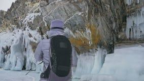 Перемещение женщины на льде Lake Baikal Отключение к острову зимы Девушка идет на ногу утесов льда Путешественник смотрит акции видеоматериалы