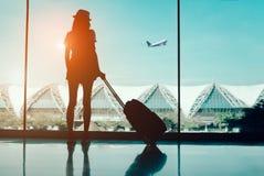 Перемещение женщины силуэта при багаж смотря без окна на international крупного аэропорта или подростке девушки путешествуя в vac