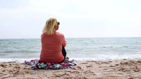 Перемещение и каникулы Взрослая белокурая женщина сидит на море и ослабляет сток-видео