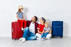 Перемещение и туризм концепции счастливая семья с чемоданами приближает к w стоковая фотография rf