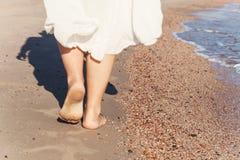 перемещение каникул - крупный план ноги женщины идя на белое relaxi песка Стоковые Изображения RF