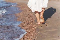перемещение каникул - крупный план ноги женщины идя на белое relaxi песка Стоковое Фото