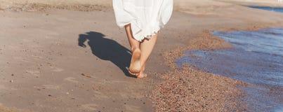 Перемещение каникул - крупный план ноги женщины идя на белый песок ослабляя в beachwear pareo маскировки пляжа Сексуальные и заго Стоковое фото RF
