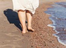 перемещение каникул - крупный план ноги женщины идя на белый песок ослабляя Стоковые Изображения