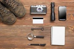 Перемещение, концепция каникул Камера, блокнот, ручка, кредитная карточка, поставки и фотография на таблице стола офиса деревянно Стоковые Изображения RF