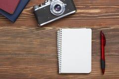 Перемещение, концепция каникул Камера и поставки на таблице стола офиса деревянной Взгляд сверху с космосом экземпляра для текста Стоковое фото RF