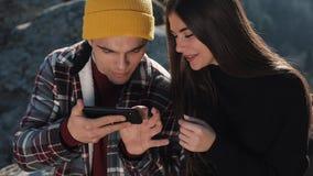 Перемещение к горам Красивая пара в любов сидит на утесе и карта использования на смартфоне Человек показывает девушку сток-видео