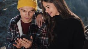 Перемещение к горам Красивая пара в любов сидит на утесе и карта использования на смартфоне Человек показывает девушку видеоматериал