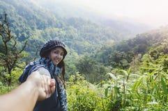 Перемещение летних каникулов пар Женщина идя на романтичные праздники держа руку жены следовать ей на сценарных горах лета стоковые изображения