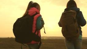Перемещение мамы и дочери с рюкзаком на заходе солнца Девушки в походе Туристы мать и ребенок идут к заходу солнца в видеоматериал