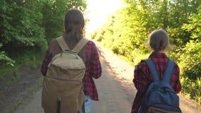 Перемещение мамы и дочери с рюкзаком против неба туристы мать и ребенок идут к заходу солнца в горах t видеоматериал
