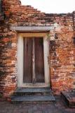 Перемещение Таиланд - старая дверь деревянная и кирпич стены как предпосылка в Wat Phutthaisawan Стоковая Фотография RF