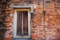 Перемещение Таиланд - старая дверь деревянная и кирпич стены как предпосылка в Wat Phutthaisawan Стоковые Изображения RF