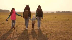 Перемещения семьи с собакой через равнины и горы мать, дочери и домашние туристы любимцев сыгранность a акции видеоматериалы