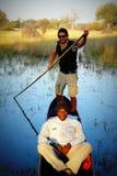 Перепад Okavango, Ботсвана - 14-ое июля 2012: Местные гиды и туристы едут традиционные вызванные шлюпки mokoros ища для живой при Стоковая Фотография