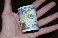 Переплетенная пачка 100 долларовых банкнот в руке Стоковое Изображение