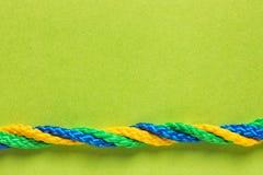 Переплетенные веревочки на предпосылке цвета Стоковое фото RF