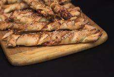 Переплетенные ручки хлеба сыра с семенами ветчины и сезама на деревянной доске стоковое изображение