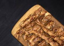 Переплетенные ручки хлеба сыра с семенами ветчины и сезама на деревянной доске стоковое фото rf