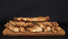 Переплетенные ручки хлеба сыра с семенами ветчины и сезама на деревянной доске стоковая фотография