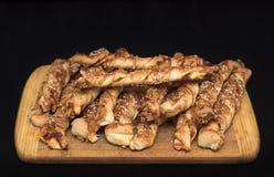 Переплетенные ручки хлеба сыра с семенами ветчины и сезама на деревянной доске стоковые изображения rf