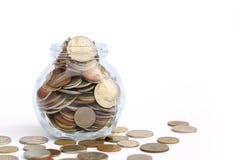 Переполняя опарник международных монеток на белой предпосылке с космосом экземпляра стоковые фотографии rf