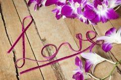 Переплетенная влюбленность слова ленты на древесине с орхидеями стоковое фото rf