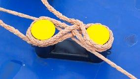 Переплетенная оранжевая веревочка вокруг желтого пала Стоковые Фото