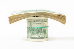 Переплетенная пачка 100 долларовых банкнот стоит на пакетах долларов Стоковая Фотография