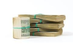 Переплетенная пачка 100 долларовых банкнот стоит на пакетах долларов Стоковое Изображение RF