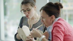 Перерыв на ланч в офисе 2 бизнес-леди едят китайские лапши и связывают положение на окне сток-видео