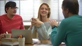 Перерыв на чашку кофе Молодые люди выпивая кофе и говоря в офисе сток-видео