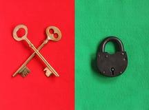 2 пересекли золотые ключи на войлоке красного цвета и padlock конца на зеленом f Стоковые Фото