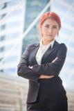 Пересеченные оружия бизнес-леди усмехаясь Стоковые Изображения