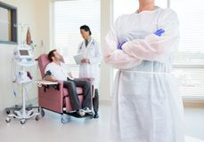 Пересеченные оружия медсестры стоящие пока доктор Examining Стоковые Фотографии RF