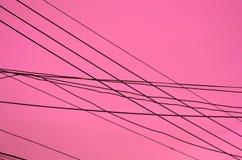 Пересеченные провода над темной розоватой предпосылкой Стоковые Фото