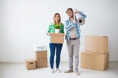 Перестановка, новый дом и концепция недвижимости - молодая пара upacking в их новой квартире совместно стоковые фотографии rf