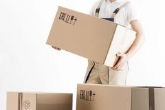 Перестановка обслуживает концепцию Движенец держа картонную коробку изолированный на белой предпосылке Затяжелитель в коробке нос стоковые изображения rf