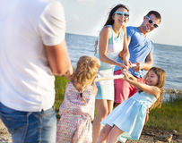 Перетягивание каната - семья играя на пляже пристаньте солнце к берегу лета взморья lounger праздника Англии палубы дня стула bri Стоковая Фотография