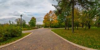 Переулок конкретных плиток в парке города осени под облачным небом Стоковая Фотография