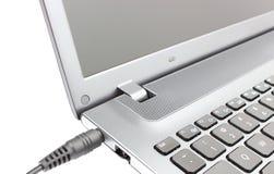 Переходника штепсельной вилки будучи подключанным к портативному компьютеру Стоковое Изображение RF