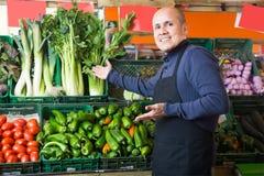 Перец активного продавца предлагая в vegetable отделе Стоковые Изображения RF