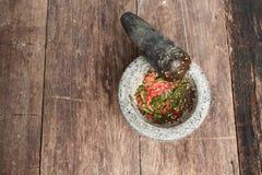 Перец чилей в каменном миномете на деревянном столе Стоковые Изображения