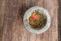 Перец чилей в каменном миномете на деревянном столе Стоковое Изображение RF