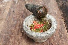 Перец чилей в каменном миномете на деревянном столе Стоковые Фото