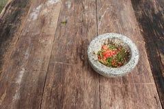Перец чилей в каменном миномете на деревянном столе Стоковое Изображение