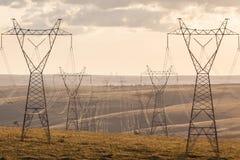 Передающие линии высоковольтного столба высоковольтные на заходе солнца Стоковые Изображения RF
