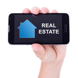 Передвижной умный телефон с применением недвижимости в изолированной руке Стоковые Фото