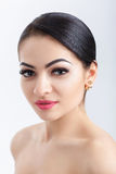 Передний портрет привлекательной молодой женщины брюнет на серой предпосылке очистьте кожу девушки стоковое фото