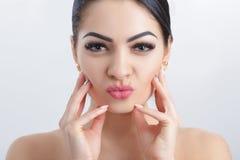 Передний портрет привлекательной молодой женщины брюнет на серой предпосылке очистьте кожу девушки стоковая фотография